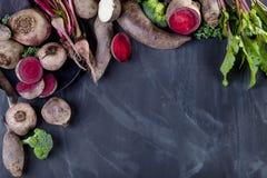 Olika grönsaker på svart med plattan Arkivbild