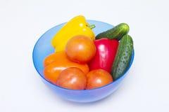 Olika hela grönsaker av olika färger i en bunke för en sallad Arkivbild