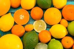 Olika hela och skivade citrusfrukter på den blåa trätabellen Royaltyfri Foto