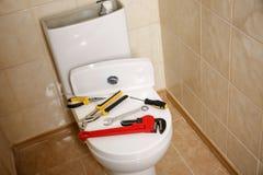 Olika hjälpmedel för rörmokare` s på locket för toalettplats royaltyfri foto