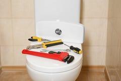 Olika hjälpmedel för rörmokare` s på locket för toalettplats royaltyfri fotografi