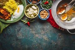 Olika indiska matskålar med curry, yoghurt, ris, bröd, höna, chutney, paneerost och kryddor på mörk lantlig bakgrund, till arkivfoto