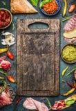 Olika ingredienser för bruschetta- eller crostinidanande: rökt kött, korv, skinka, pesto, torra tomater, peperoni runt om tomt ga royaltyfri foto