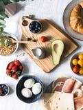 Olika ingredienser för en omväxlande frukostost, prosciuttoen, körsbärsröda tomater, avokadot, ägg, granola, mjölkar, bär som är  arkivfoto
