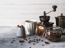 Olika ingredienser för framställning av kaffe, av exponeringsglaskruset med kaffebönor, socker, tappningkaffekanna, kaffekvarn, k royaltyfria foton