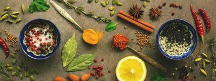 Olika kryddor, örter och smaktillsatser för att laga mat på en mörk brun bakgrund Bästa sikt, baner royaltyfri fotografi