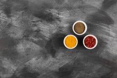 Olika kryddor i bunkar på svart bakgrund Bästa sikt, kopieringsspac Arkivbild