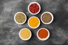 Olika kryddor i bunkar på svart bakgrund Top beskådar Matbaksida Arkivbild