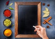 Olika kryddor nära svart tavla på bakgrund för blå sten Fotografering för Bildbyråer