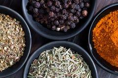 Olika kryddor och örter i skedar eller bunkar på en träbrunt Royaltyfri Foto