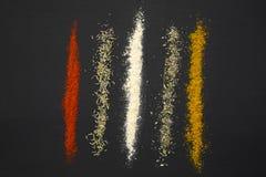 Olika kryddor och örter på en svart fotografering för bildbyråer
