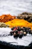 Olika kryddor och örter på en svart kritiserar indiska kryddor Ingredienser för matlagning äta för begrepp som är sunt Olika kryd royaltyfri foto