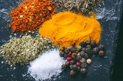 Olika kryddor och örter på en svart kritiserar indiska kryddor Ingredienser för matlagning äta för begrepp som är sunt Olika kryd royaltyfri fotografi