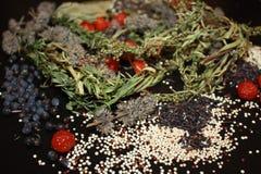 Olika kryddor på svart träbakgrund med fulled glass banker arkivfoto