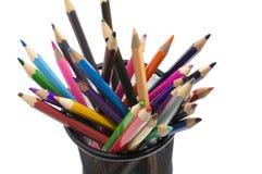 Olika kulöra blyertspennor som står i grillad blyertspennakopp Royaltyfri Foto