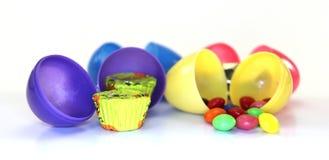 Olika kulöra easter ägg med godisen inom Arkivbilder