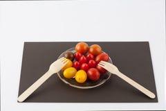 Olika kulöra körsbärsröda tomater och kulinarisk compositi för två gafflar Fotografering för Bildbyråer