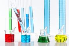 Olika laboratoriumflaskor med kulöra agens, pipett Arkivfoto