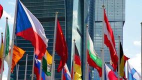 Olika landsflaggor som vinkar nära skyskrapa stock video