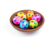 Olika målade fega easter ägg i träbunke på vit fotografering för bildbyråer