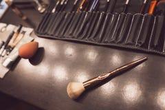 Olika makeupborstar på den mörka tabellen royaltyfri fotografi