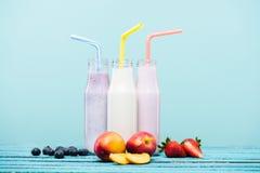 Olika milkshakar i glasflaskor och nya frukter på trätabellen arkivfoto