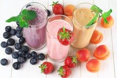 Olika milkshakar med frukter arkivbilder