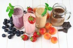 Olika milkshakar med frukter arkivfoto