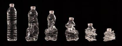 Olika moment av att pressa en plast- flaska samman Arkivfoton