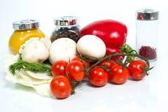 Olika nya grönsaker, champinjoner och kryddor på vitbackgro Arkivfoton