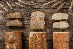 Olika nytt bröd och spikelets av vete på lantlig träbakgrund Idérik orientering som göras av bröd arkivbilder