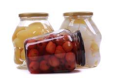 Olika på burk frukter i glasflaskor royaltyfri bild