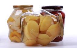 Olika på burk frukter i glasflaskor arkivfoto