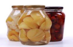 Olika på burk frukter i glasflaskor royaltyfri fotografi