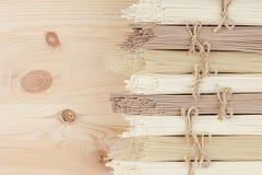 Olika packar av rå asiatiska nudlar stänger sig upp på beige träbrädebakgrund, bästa sikt Royaltyfri Fotografi