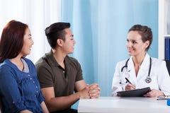 Olika par under medicinsk tidsbeställning Fotografering för Bildbyråer