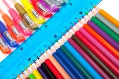 Olika pennor och blyertspennor som isoleras på vit bakgrund Royaltyfri Bild