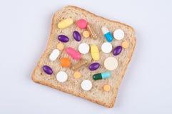 Olika piller, minnestavlor och kapslar av medicin som överträffar på det skivade brödarket; mat påverkar hälsa som medicinbegrepp arkivfoto