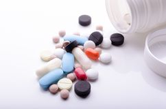 Olika piller spridde från en pillerflaska royaltyfri foto