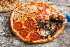 olika pizzatoppningar Italiensk pizza med olika slag av ost, grönsaker och kött på gammalt träbakgrundsslut upp Fotografering för Bildbyråer