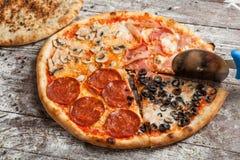olika pizzatoppningar Italiensk pizza med olika slag av ost, grönsaker och kött på gammalt träbakgrundsslut upp Royaltyfri Foto