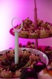 Olika plattor med kakor med purpurfärgad bakgrund Arkivfoton