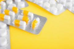 Olika preventivpillerar och minnestavlor på en ljus gul bakgrund Orange och vita smärtstillande medel för närbild och ljusa antib Royaltyfri Fotografi