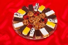 Olika söta tårtor på runda pläterar Arkivbilder