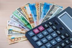 Olika sedlar av olika valörer staplas i en fan och en räknemaskin på tabellen royaltyfri bild