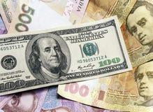 Olika sedlar för bakgrund av oss dollar och ukrainsk hryvnia Fotografering för Bildbyråer