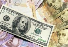Olika sedlar för bakgrund av oss dollar och ukrainsk hryvnia Arkivbilder