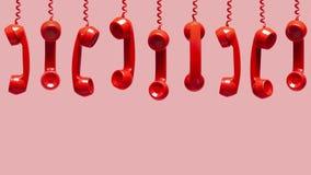 Olika sikter av gamla röda telefonmottagare som hänger på rosa bakgrund arkivbild