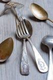 Olika skedar och gafflar flätade ihop på den lantliga trätabellen Arkivbild