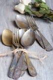 Olika skedar och gafflar flätade ihop på den lantliga trätabellen Royaltyfri Fotografi